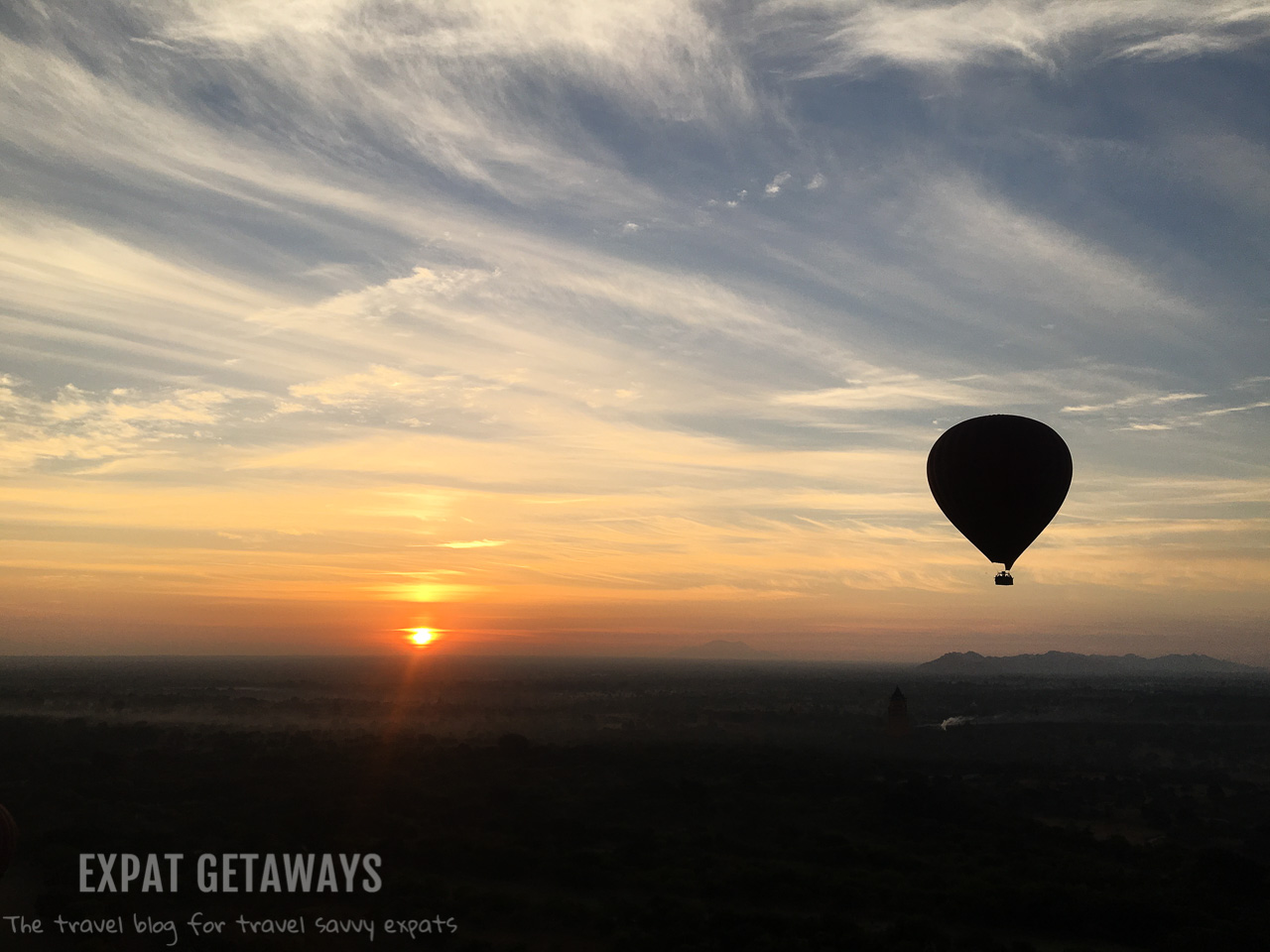 The first balloon lifts into the air as the sun starts to rise.