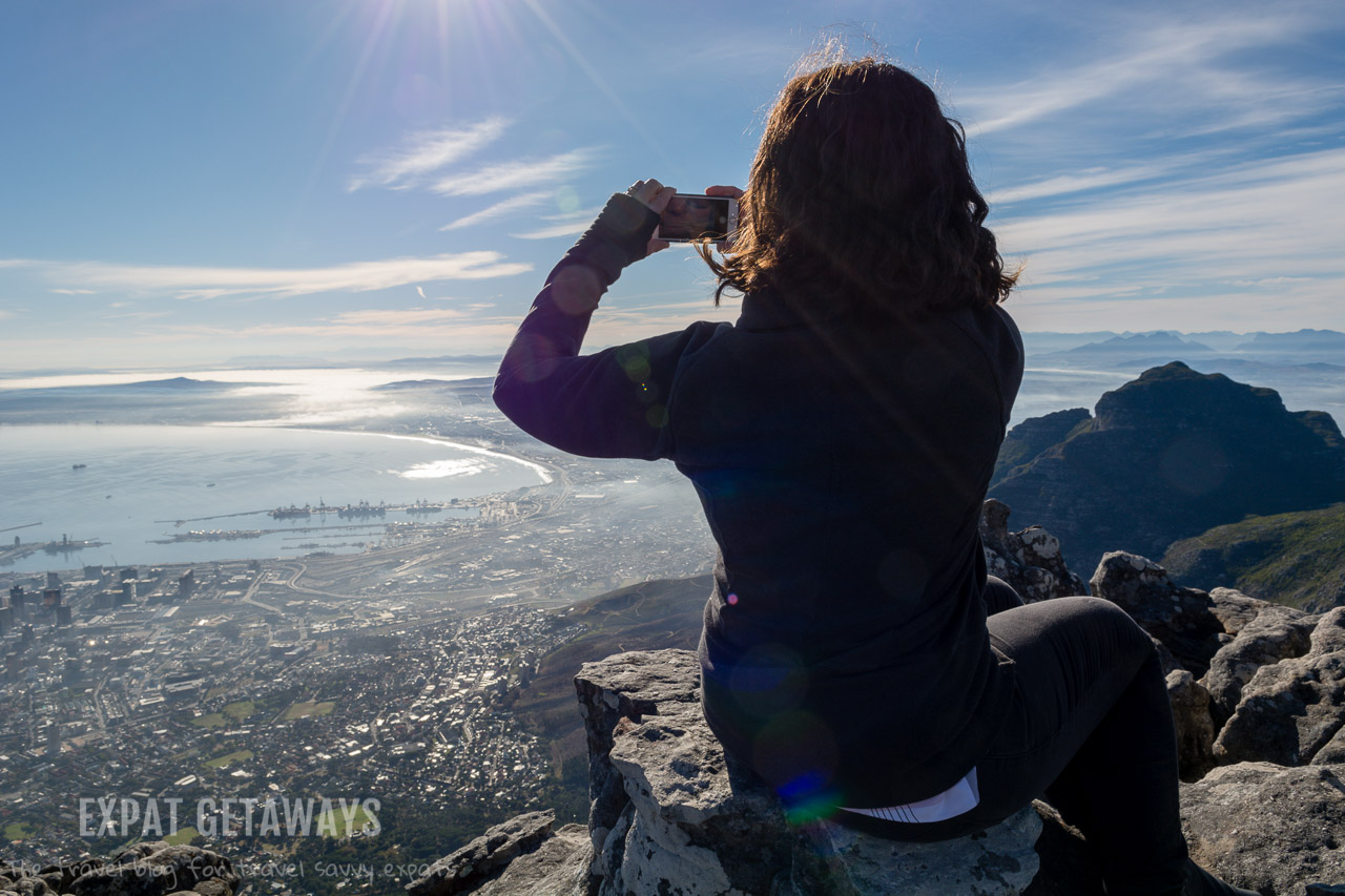Don't drop the phone! Jess taking photos of the breathtaking view from Table Mountain, Cape Town. Expat Getaways Expat Getaways One Week in Cape Town.