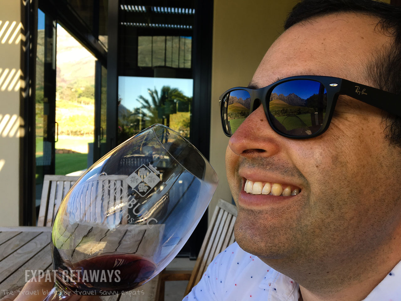 Andrew enjoying a glass of red wine in the Franschhoek wine region just outsite of Cape Town. Expat Getaways 2 Weeks in Southern Africa.