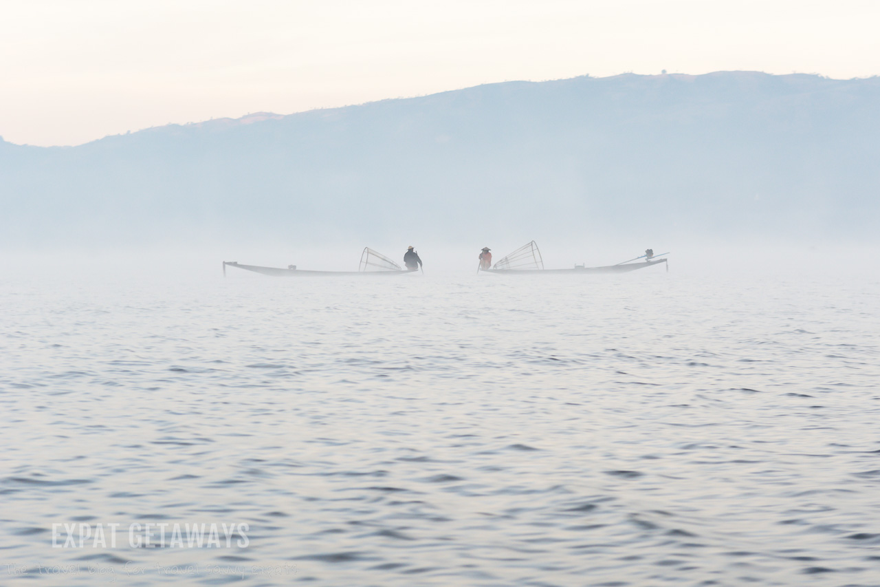 Fishermen sit and talk on their small boats early in the morning, surrouned by morning fog on Inle Lake, Myanmar.