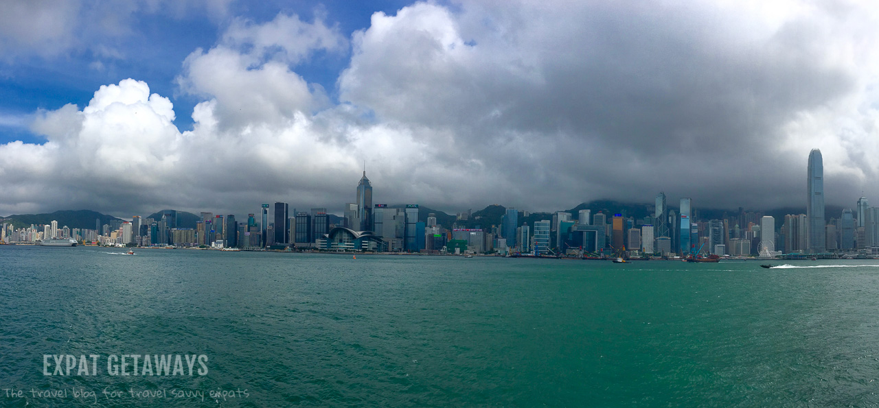 Dark clouds roll in over the Hong Kong skyline. Hong Kong weather in summer is unpredictable at best. Expat Getaways, First Time Hong Kong Survival Guide - Weather and Seasons.