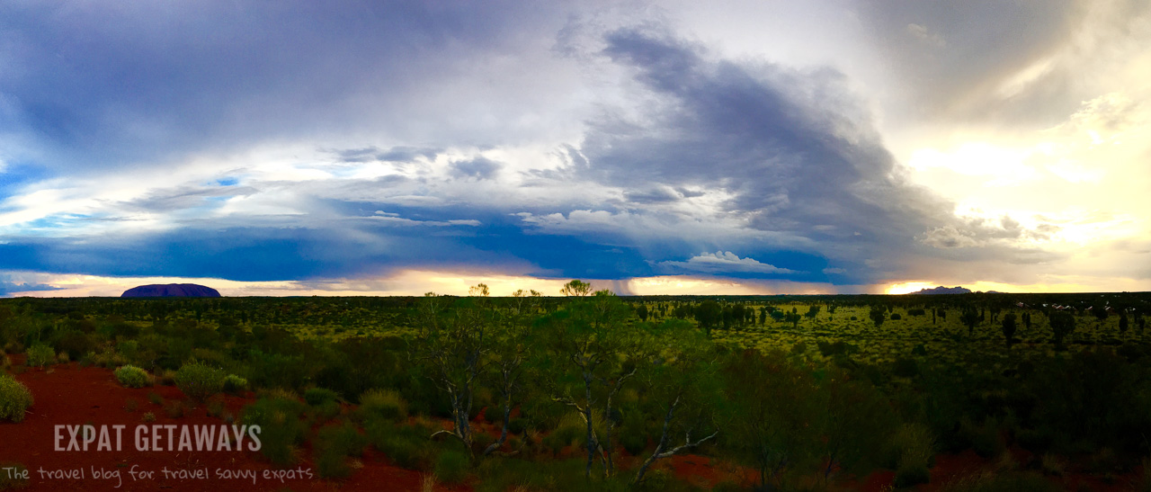 Watching the storms roll through the desert between Kata-Tjuta and Uluru from the top of a sand dune. Expat Getaways - Babymoon Destinations.